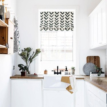 white kitchen with butcher block countertops and patterned roman shade