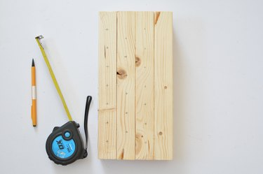 Measuring drill holes on wooden bee house