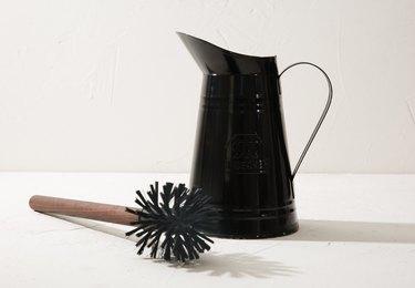 A black handled jar and a brush