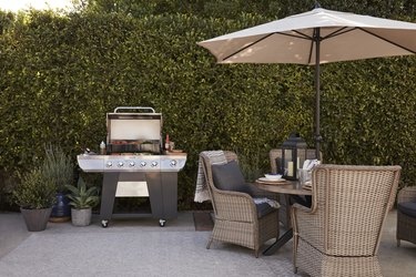Outdoor grill near dining table and umbrella