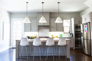 Tonal gray kitchen colors with white Eames style bar stools