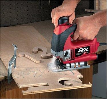 Jig saw cutting wood numbers.
