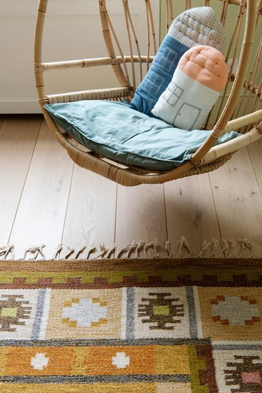 patterned ochre color rug in room with wood hanging chair