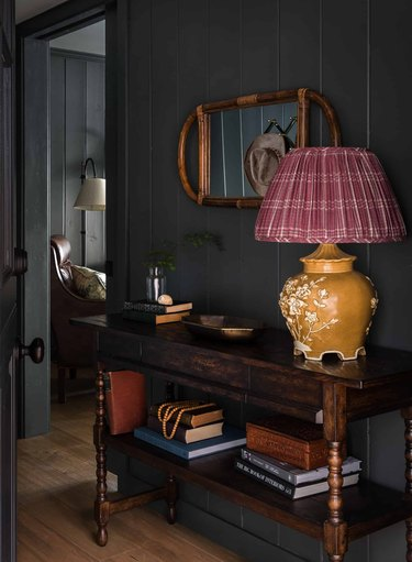 Entryway with shiplap, ceramic lamp with checked lampshade, credenza, books, cane mirror.