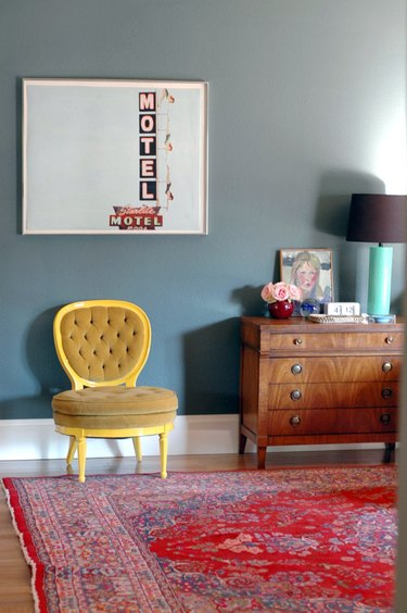 ochre color accent chair in green room with red vintage rug