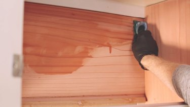 Wiping boiled linseed oil on cabinet