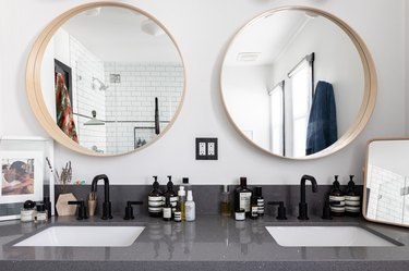 gray stone countertop, double undermount sinks with black faucets and handles, two round mirrors with wood trim, reflection of white subway tile shower