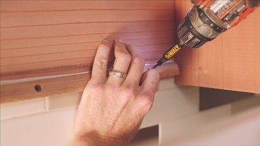 Attaching cedar support beam inside cabinet