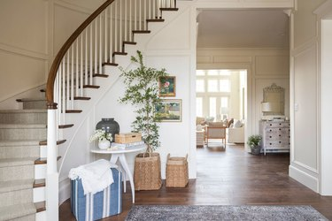 curved grand traditional staircase looking down over entryway table and potted tree
