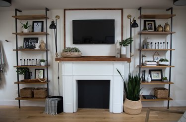 basement storage ideas with rustic metal shelving, fireplace, flat screen, and wood floors