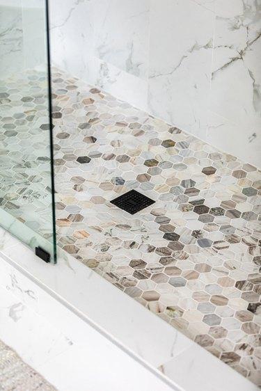 black shower drain, multicolored hexagon shower floor tile, marble wall tile, glass shower door