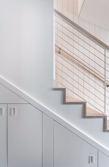 basement storage ideas with white built-in cabinets below stairs