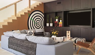basement storage ideas with black built-in shelves and media unit with flat screen