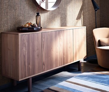 basement storage ideas with natural wood credenza, round mirror, and striped area rug