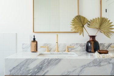 marble vanity countertop with ceramic undermount sink, gold faucet and handles, brown soap dispenser, vase with paper flowers, rectangular mirror with gold trim