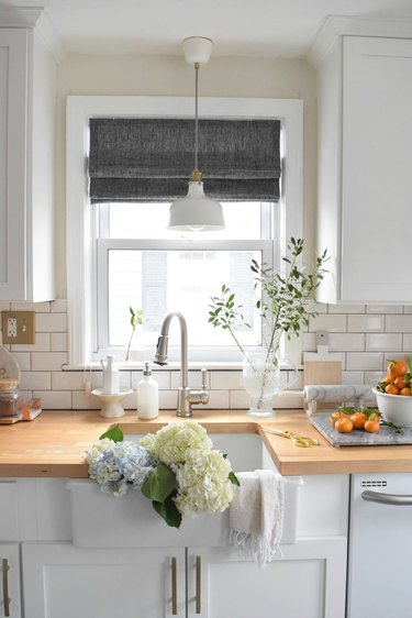 Farmhouse kitchen window with gray roman shades