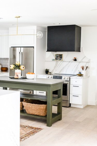 green traditional kitchen island in kitchen with marble backsplash