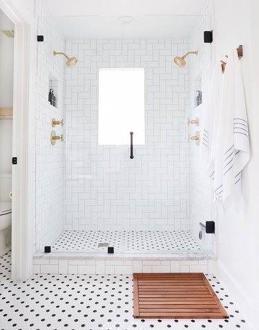 black-and-white bathroom idea with mosaic floor tile and glass shower enclosure