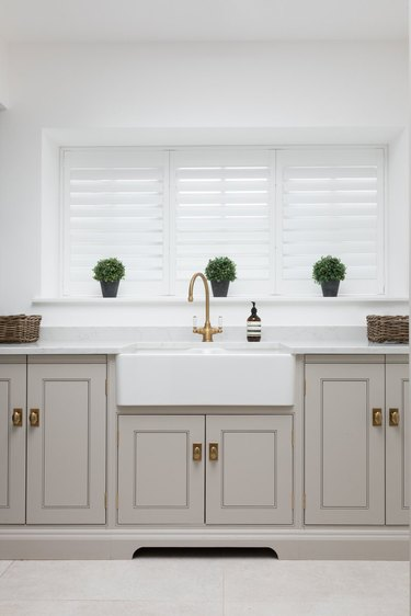 Kitchen window with tracked shutters in gray and white kitchen
