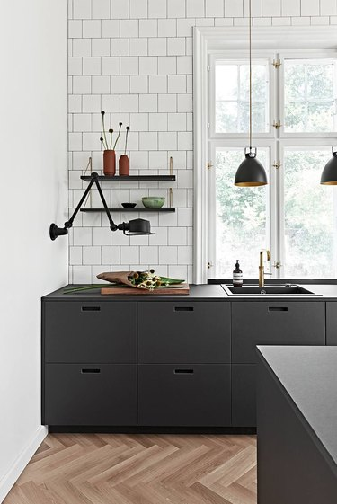 Black and white kitchen colors in kitchen with black lights and herringbone wood floor