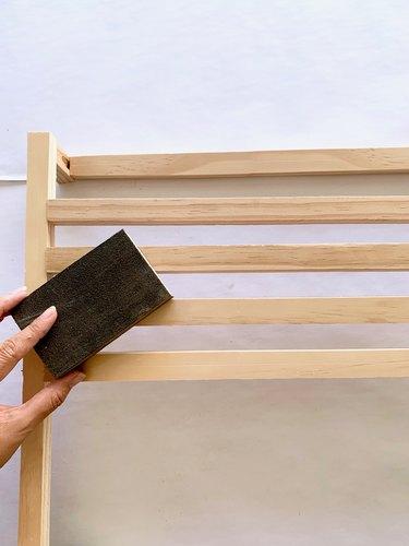 Sanding wood dowels for modern towel rack DIY