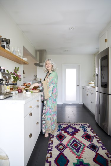 Designlovefest's Bri Emery in kitchen with white cabinets and open shelving