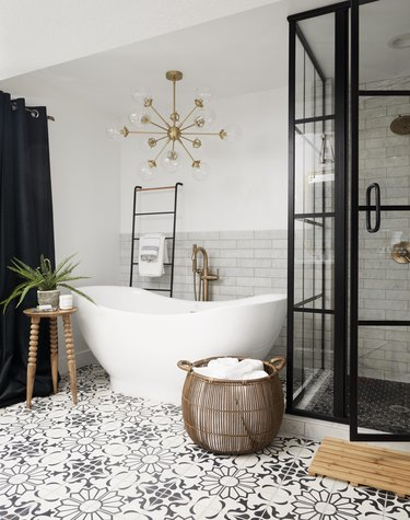 black-and-white bathroom idea with patterned floor tile and freestanding bathtub