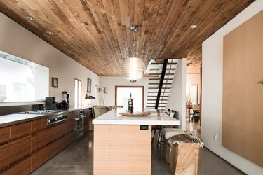 wood kitchen, wood kitchen island with white stone countertop and dark wood-paneled ceiling with hanging pendant lights