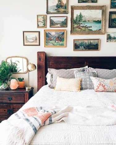 Bedroom wall decor idea with vintage oil paintings above bed