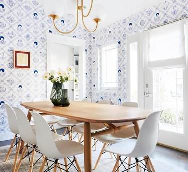 Dining room with blue and white patterned wallpaper, white midcentury dining chairs, and rounded rectangular wooden dining table