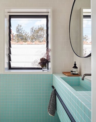 Aqua tile bathroom sink idea with white tile and round mirror