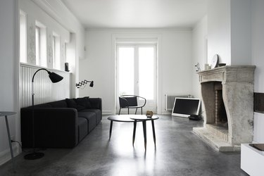 minimalist black-and-white living room idea with black sofa and stone fireplace