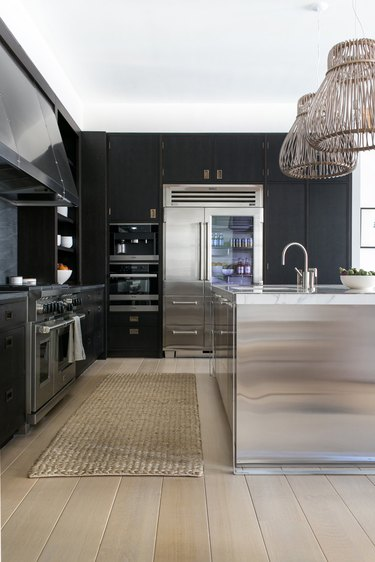 black kitchen cabinet idea for a modern kitchen with flloor-to-ceiling black cabinets, stainless steel appliances, and a stainless steel island
