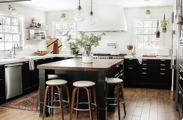 black kitchen cabinet idea for a large kitchen with white walls, lots of windows, lower black cabinets, and a black island with a wood countertop