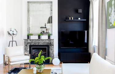 black-and-white living room idea with wood floors and black TV wall