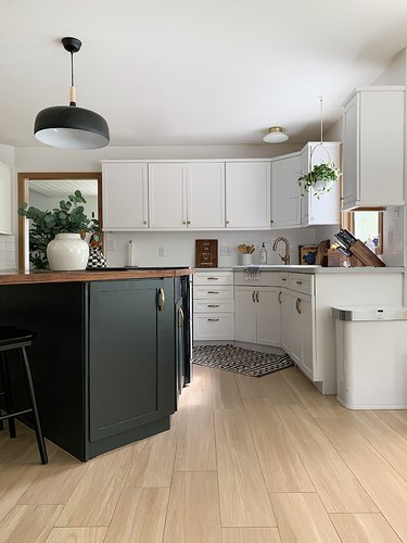 black kitchen cabinet idea for mostly white kitchen with a black island featuring a walnut countertop situated at an angle under a black pendant light
