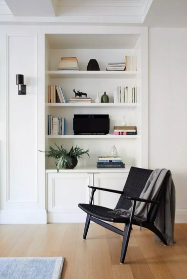 black-and-white living room idea with black accent chair and built-in bookcase