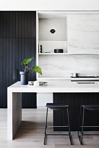 black kitchen cabinet idea with island and marble backsplash