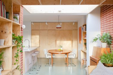 colors that go with red in a white room with plywood shelves and brick red wall