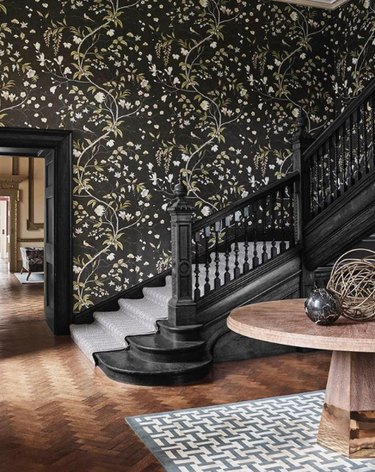 traditional staircase and floral wallpaper and black railing
