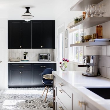 black kitchen cabinet idea for kitchen with light cabinets in the foreground and black cabinets in the background