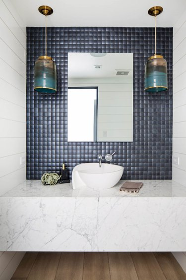bathroom backsplash idea with navy square tile with frameless mirror and hanging pendant lights
