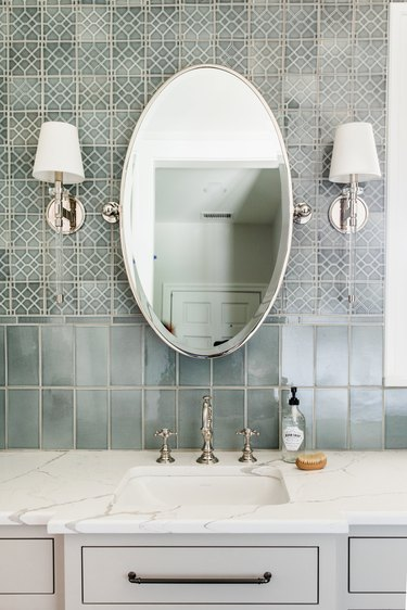 bathroom backsplash idea with different tile and oval mirror framed by wallsconces