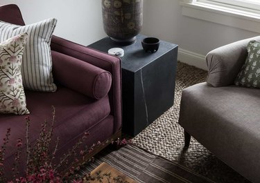 neutral carpet colors in living room with grasscloth flooring and purle couch