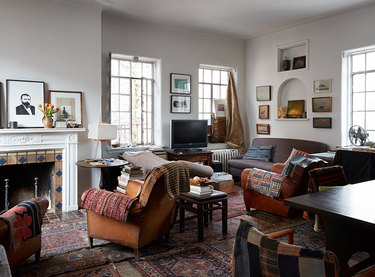 patterned carpet colors in living room with multiple rugs and leather arm chairs