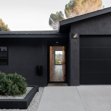black traditional stucco homes with concrete driveway