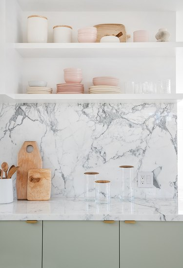 marble kitchen backsplash with open shelving and green cabinets