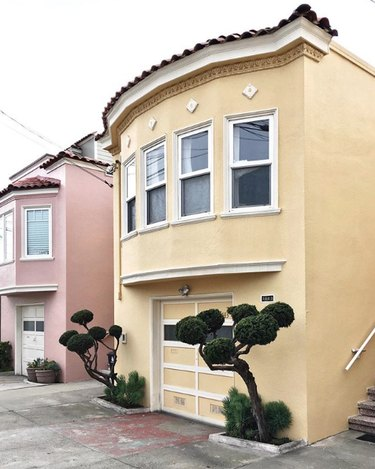 Yellow traditional stucco homes in row of townhouses