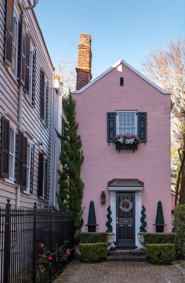 pink traditional stucco homes with topiaries and brick walkway