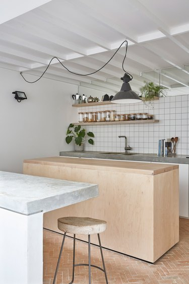 full height grid kitchen backsplash with wood island and concrete countertops